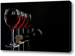 Силуэты нескольких бокалов с вином и бутылкой на черном фоне