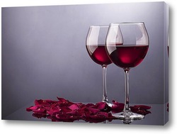 Два бокала с вином и лепестки роз